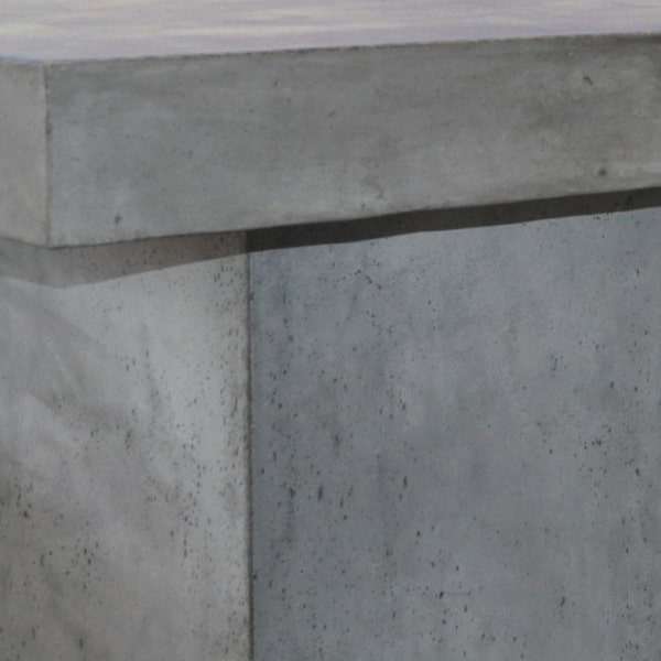 blok raw concrete dining table with 3 pedestals closeup