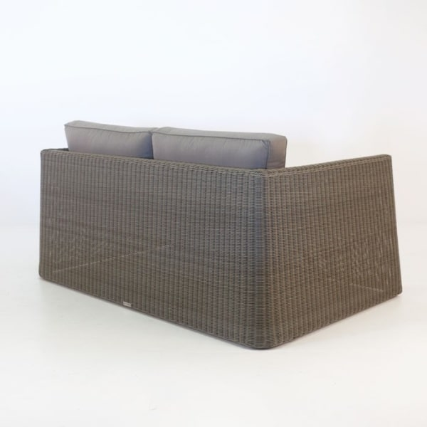 brown wicker loveseat with cushions