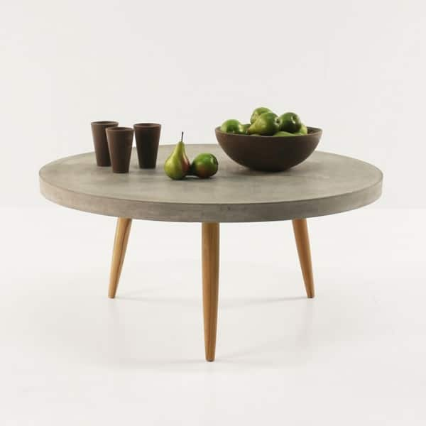concrete table with cups and a bowl of pears
